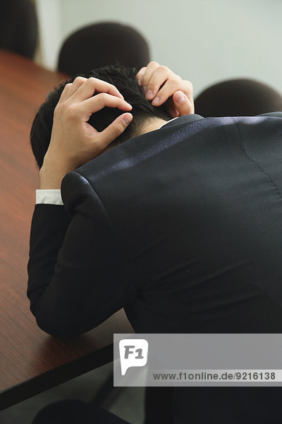 Desperate Japanese young businessman in a suit