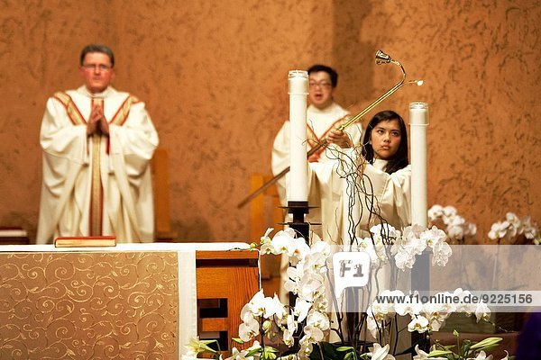 A young Hispanic altar server lights ceremonial candles at St. Timothy's Catholic Church  Laguna Niguel  CA  at the start of the Solemn Liturgy of Good Friday. Note pastor and Vietnamese assistant pastor in vestments.