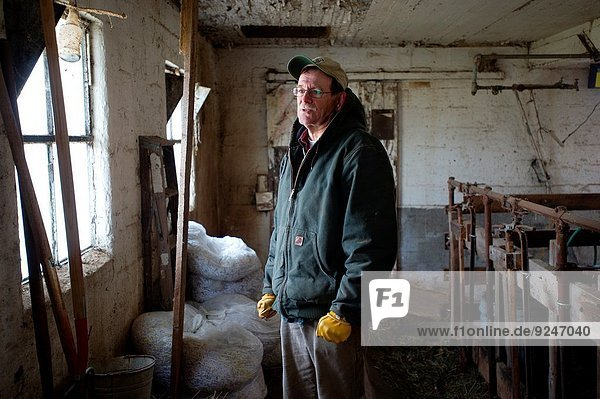 Farmer stands illuminated by window.