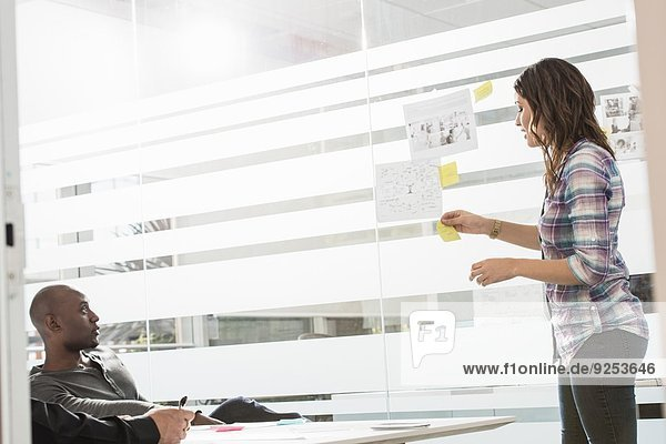 Young businesswoman presenting ideas to male colleagues