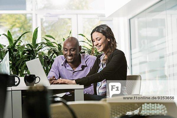 Männliche und weibliche Geschäftskollegen mit Laptop im Büro