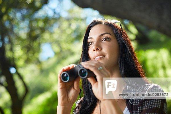 Mittlere erwachsene Frau mit Fernglas Vogelbeobachtung im Wald
