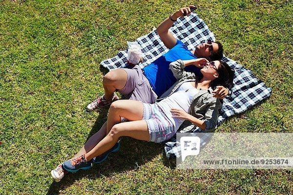 Overhead-Ansicht des Paares beim Selbstporträt auf Picknickdecke