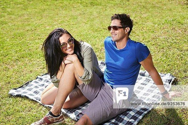 Pärchen auf Picknickdecke im Park sitzend