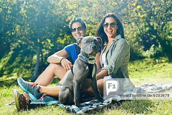Porträt eines Paares und eines Hundes auf Picknickdecke im Park