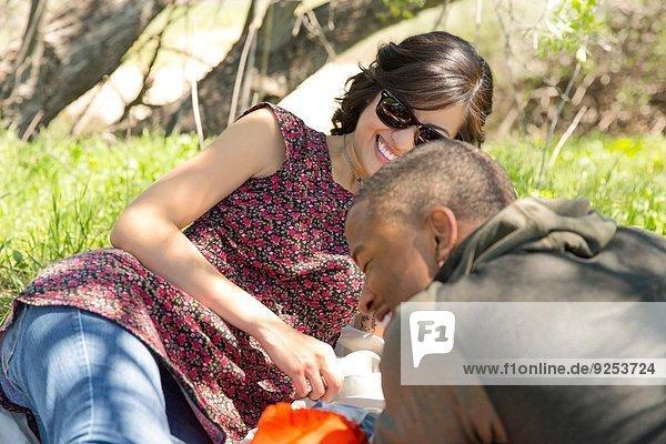Junges Paar auf Picknickdecke im Wald liegend