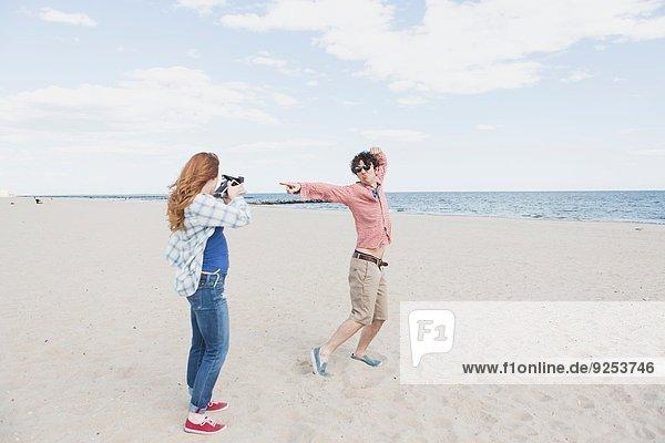 Paarfotografie mit Sofortbildkamera am Strand