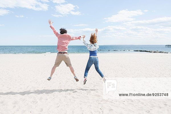 Rear view of couple jumping mid air on beach