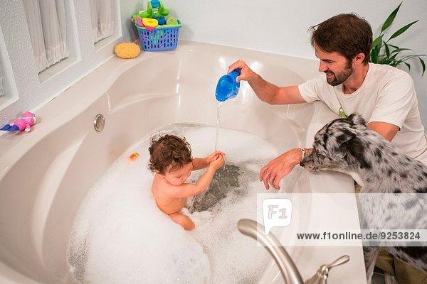 Vater spielt mit Kleinkind-Tochter im Bad