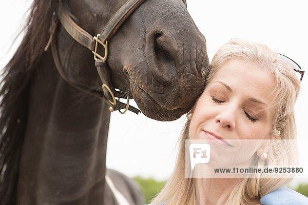 Ausschnitt aus der Nähe eines Pferdes  das das Gesicht einer reifen Frau berührt.