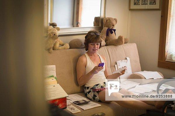 Mittlere erwachsene Frau auf dem Sofa sitzend  mit Handy
