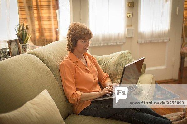 Mittlere erwachsene Frau auf dem Sofa sitzend  mit Laptop