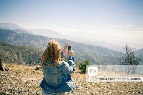 Rear view of mid adult woman photographing view on smartphone  Lake Arrowhead  California  USA