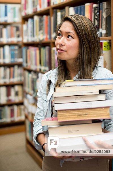Junge Frau mit Bücherstapel