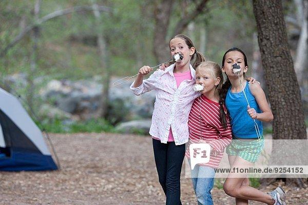 Portrait of three children eating toasted marshmallows whilst camping  Sedona  Arizona  USA