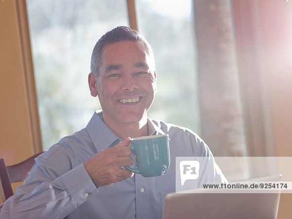 Portrait of smiling mature man with coffee and laptop