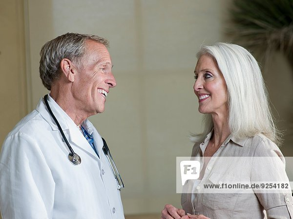 Senior male doctor reassuring mature woman patient