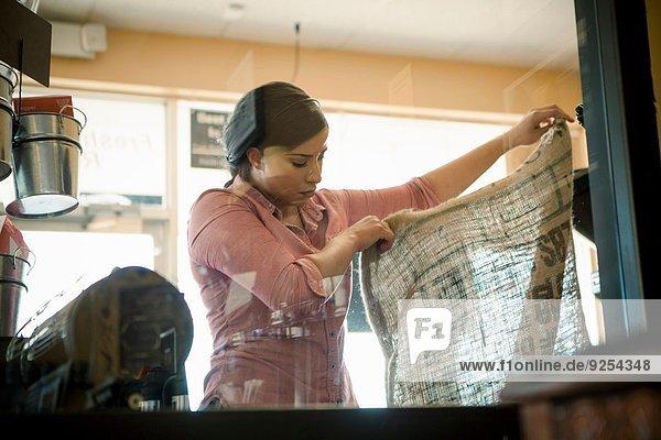 Junge Frau mit leerem Sack für Kaffeerösterei im Cafe