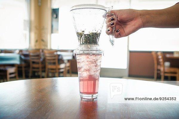 Frauenhand mit Eistee und Filter im Cafe