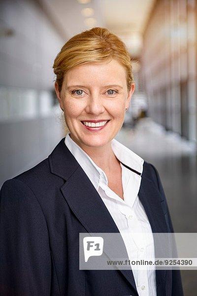 Porträt einer glücklichen reifen Geschäftsfrau im Büroflur