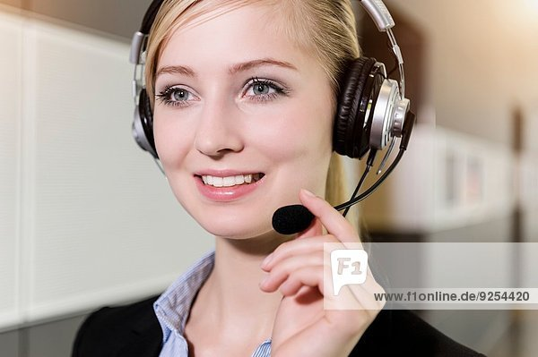 Close up portrait of young businesswoman using telephone headset