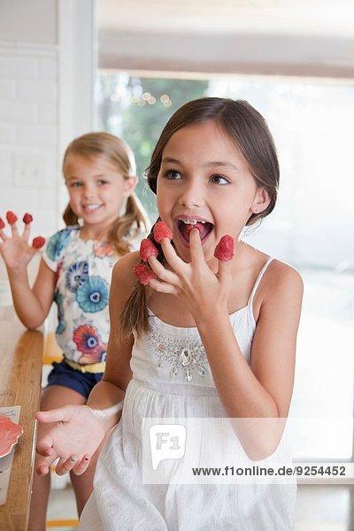 Zwei Schwestern mit Himbeeren an den Fingern in der Küche