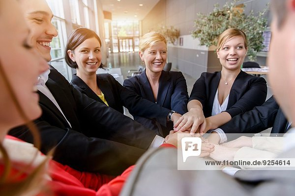 Over shoulder view of business team placing hands on top of each other in office