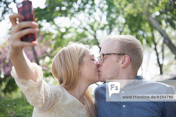 Junges Paar im Park  das sich beim Küssen selbst mitnimmt