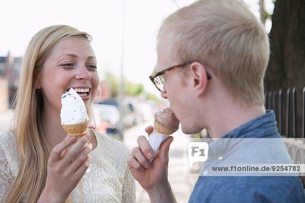 Junges Paar isst Eistüten auf der Straße