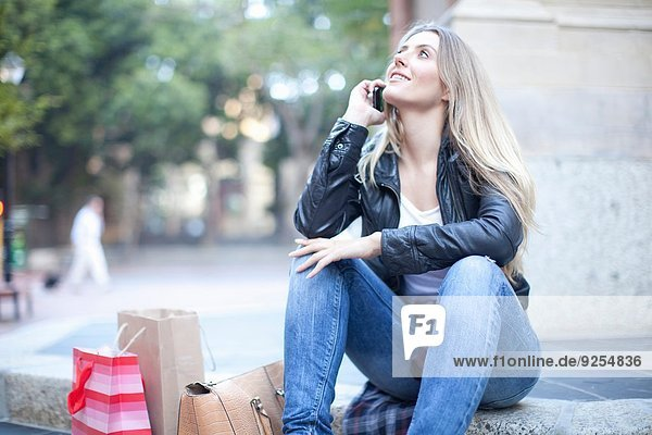Young woman shopper sitting on city steps chatting on smartphone