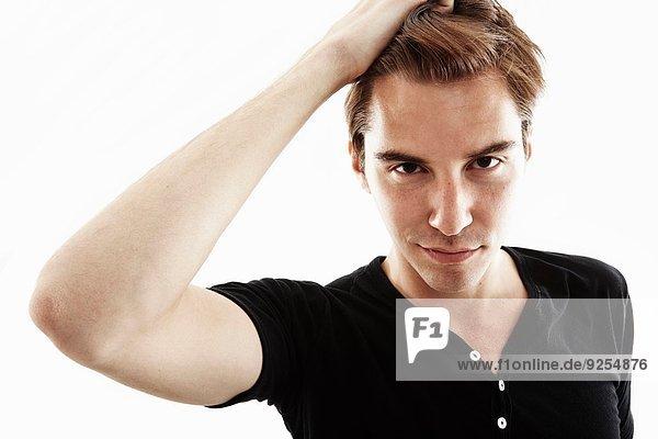 Atelierporträt eines jungen Mannes mit Hand im Haar