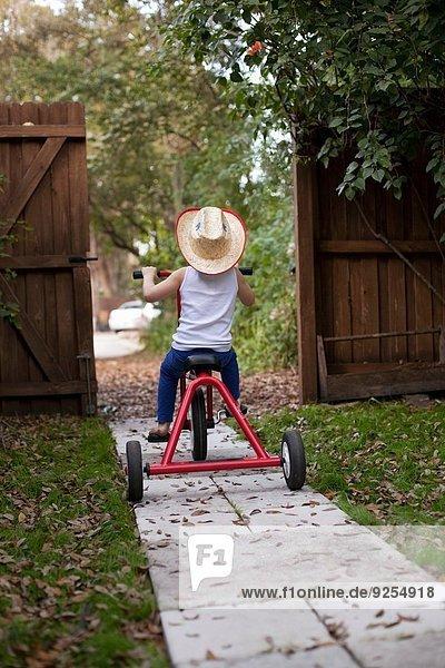 Vierjähriges Mädchen auf dem Dreirad aus dem Gartentor