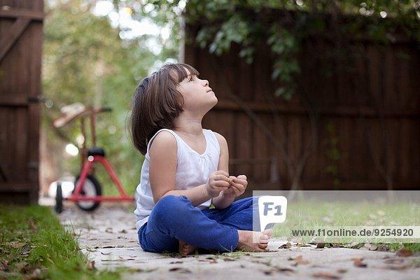 Vierjähriges Mädchen sitzt auf dem Gartenweg und blickt nach oben.