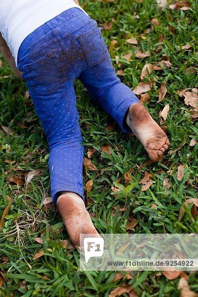 Vierjähriges Mädchen krabbelt in der Taille auf Gartengras