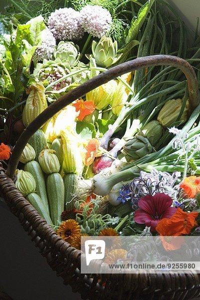 Korb mit frischem Biogemüse und Blumen