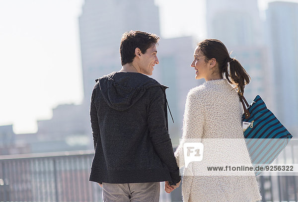 Young couple walking  buildings in background