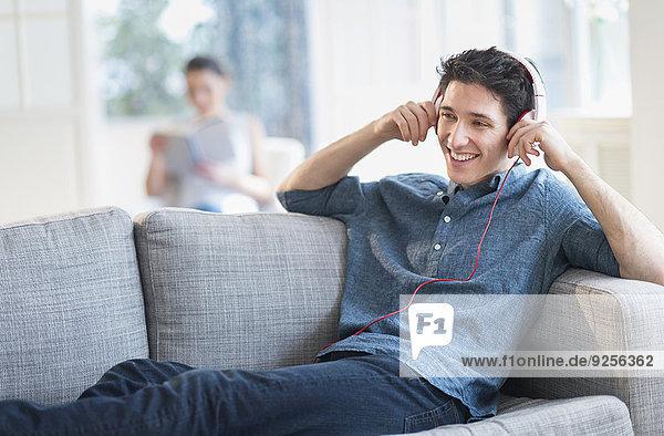 Mann zuhören Couch Musik Klassisches Konzert Klassik Frau im Hintergrund