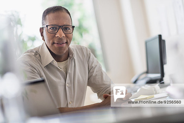 Portrait of smiling mature man working in home office