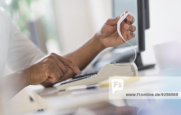 Close up of man's hands using calculator