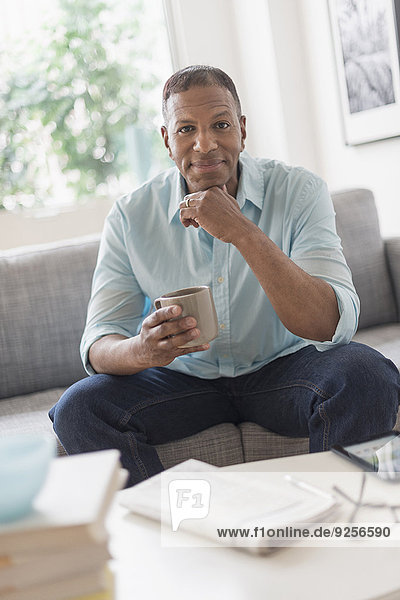 Portrait of man sitting on sofa at home