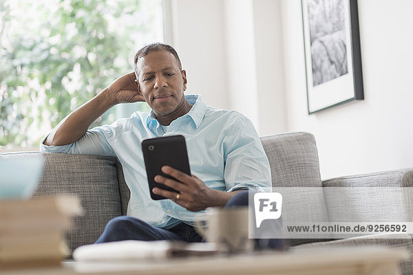 Man sitting on sofa at home and using digital tablet