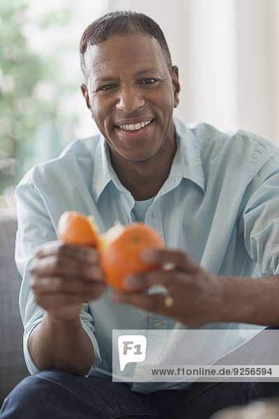 Portrait of smiling man peeling orange fruit