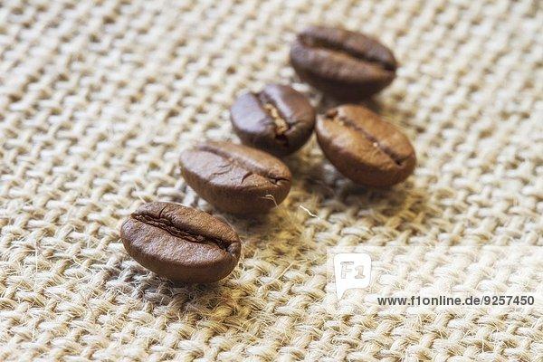 Fünf Kaffeebohnen auf Jute