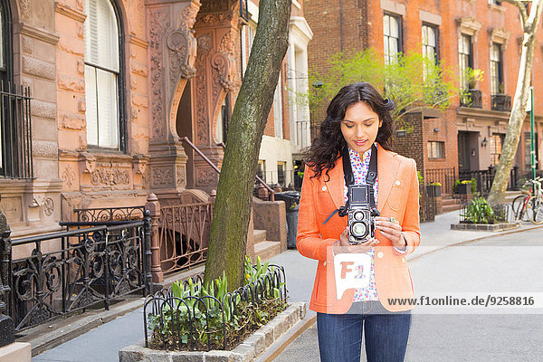 Mixed race woman taking pictures with vintage camera on city street