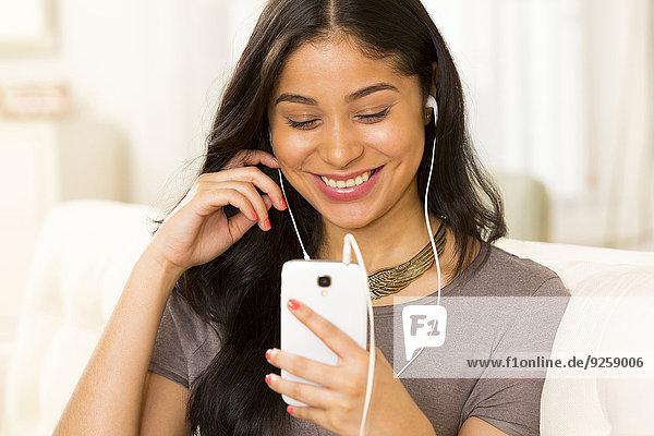 Frau zuhören Hispanier Kopfhörer