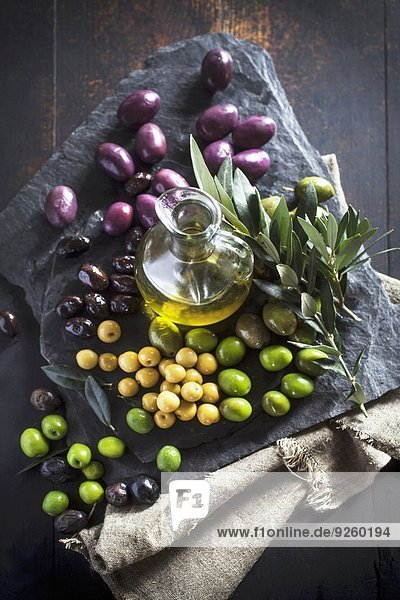 Eine Karaffe Olivenöl  verschiedene Oliven und Olivenzweig auf Steinplatte