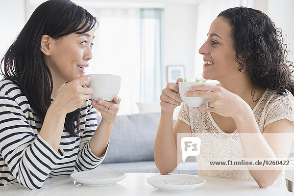 Women drinking coffee together at table
