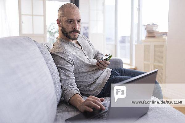 Hispanic man using cell phone and laptop on sofa