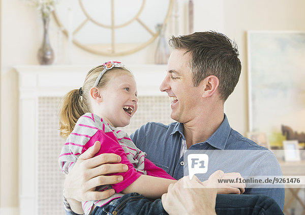 Caucasian father and daughter playing together