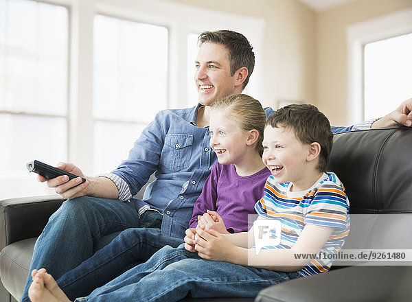 Caucasian father and children watching television on sofa